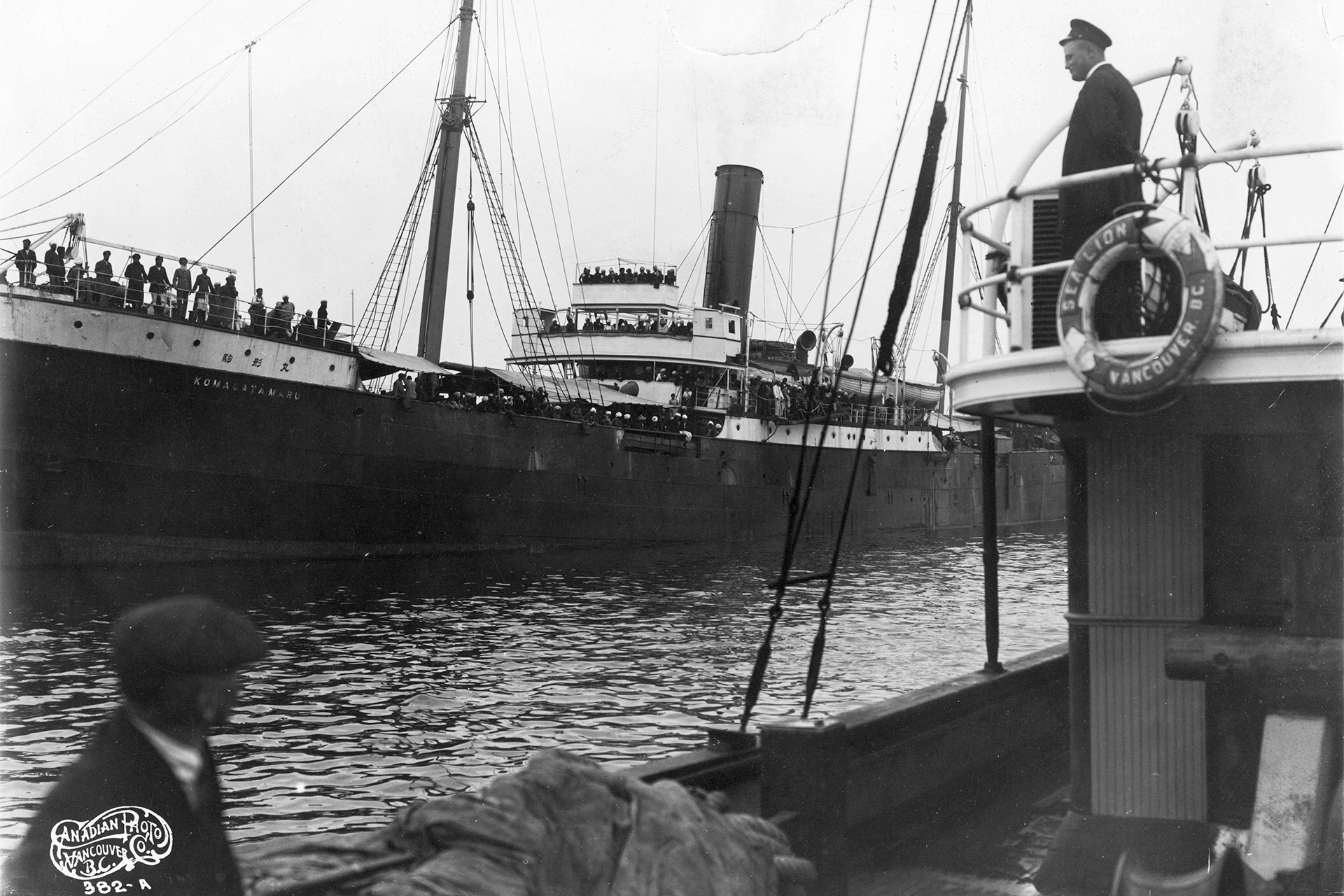 Immigration Officer keeps watch from the Sea Lion (Photo: Library and Archives Canada).